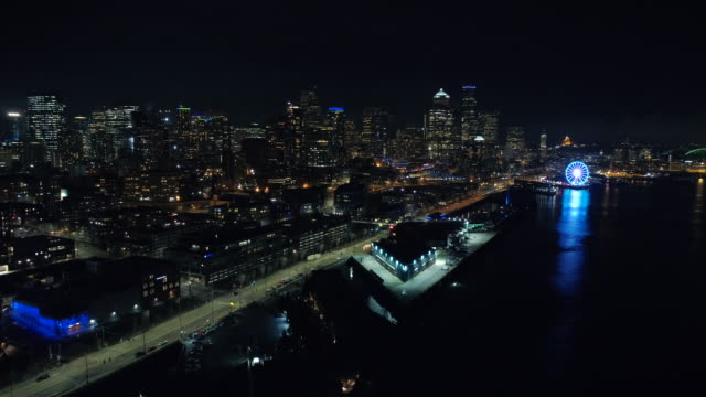 helikopterperspektiv av seattle waterfront på natten i pulserande belysning - strandnära bildbanksvideor och videomaterial från bakom kulisserna