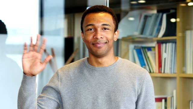 hello by young afro-american man, waving hand - machać filmów i materiałów b-roll
