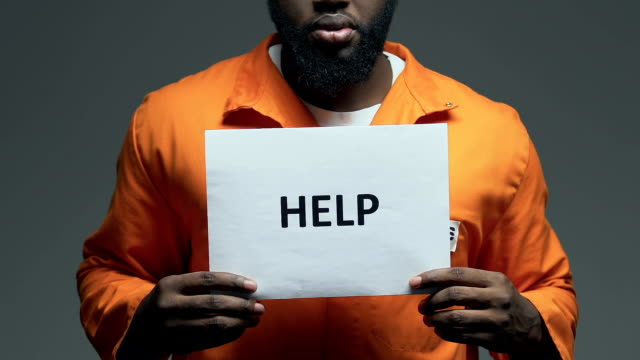 Help word on cardboard in hands of Afro-American prisoner, asking for freedom Help word on cardboard in hands of Afro-American prisoner, asking for freedom civil rights stock videos & royalty-free footage