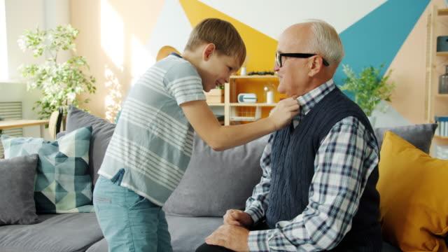 自宅で楽しんで服を着てうっとうしい祖父を助ける役に立つ孫 - 支えられた点の映像素材/bロール