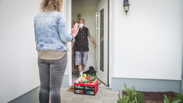 hjälpsam granne leverera färsk mat på tröskeln till en äldre man under coronavirus kris - assistans bildbanksvideor och videomaterial från bakom kulisserna