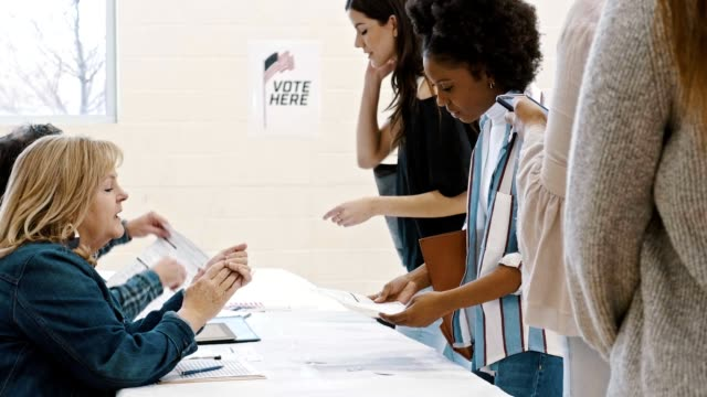 Helpful polling place volunteer helps voter on election day