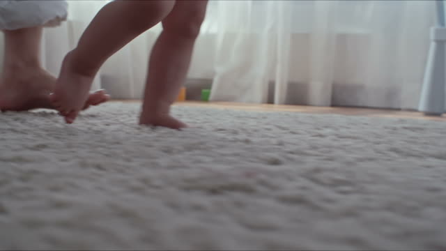 helping baby to make first steps - moquette video stock e b–roll