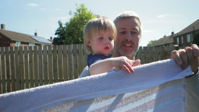 Helping Dad Hang Up the Washing