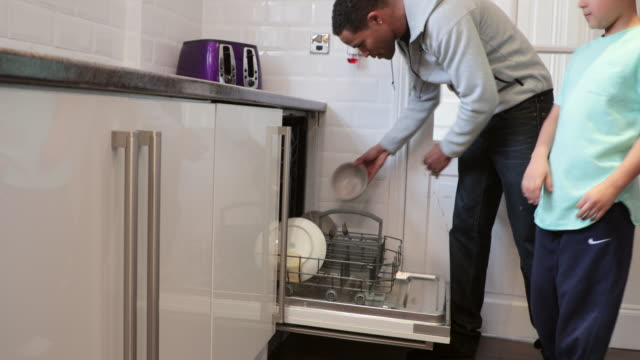 Helping Dad Load the Dishwasher Mid adult man is filling the dishwasher in the kitchen of his home with help from his son. dishwasher stock videos & royalty-free footage