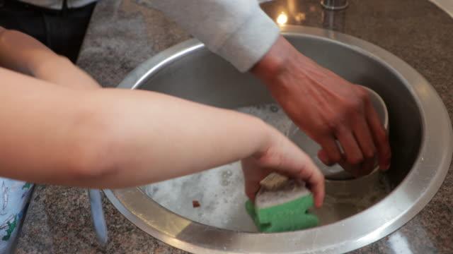 vídeos y material grabado en eventos de stock de ayudar a papá con los platos - padre que se queda en casa