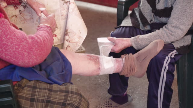 a helping hand. bandage wrap on an open wound on the leg of an old lady. medical concept. - rana filmów i materiałów b-roll