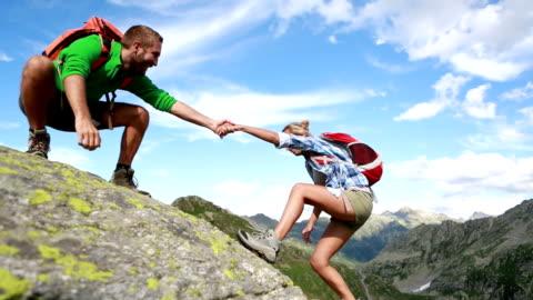 vídeos y material grabado en eventos de stock de ayudar a mano entre dos escalador: verano - miembro humano