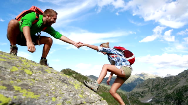 Helping hand between two climber-Summer Young woman hiking high up in the mountains reaching the top, she is pulling out her hand asking for assistance. The man is giving her a helping hand. young couple stock videos & royalty-free footage