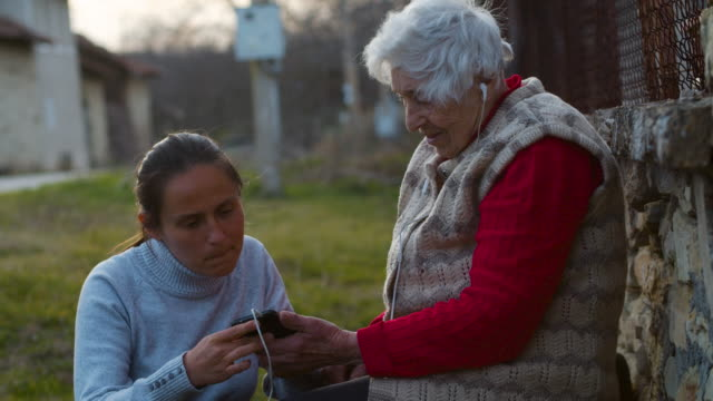 a helping hand. young woman explaining her grandmother how to listen to music with a set of headphones and a phone. - ragazza auricolari rossi video stock e b–roll