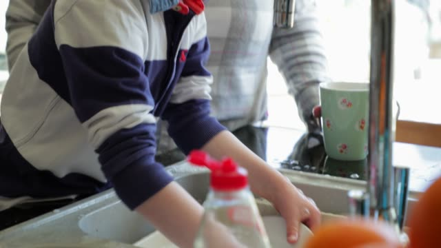 Helping Mum Wash the Dishes Little boy and his Mother washing the dishes in the kitchen sink. chores stock videos & royalty-free footage