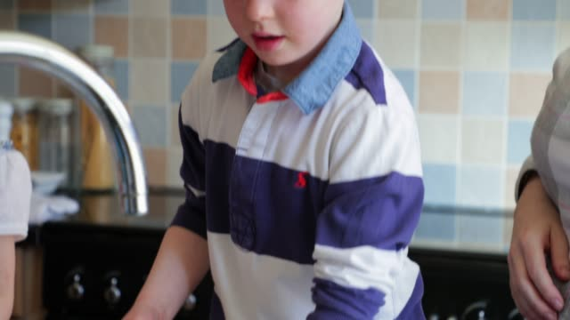 Helping Mummy with the House Work Two children and their Mother washing the dishes in the kitchen sink. dishwashing liquid stock videos & royalty-free footage