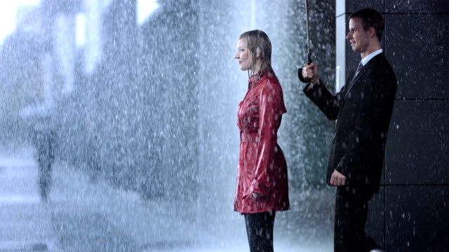Helping Umbrella HD1080p: Businesswoman in a red coat standing all wet in the rain while her colleague surprise her with an umbrella. After covering her under his umbrella,  she give him a warm hug. lost stock videos & royalty-free footage