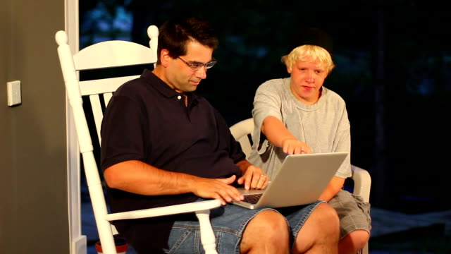Helping with Computer A boy helps his father use the computer.  Actually, that could be his uncle.  But really, it doesn't matter--right?  This is stock footage; it can be anything you need it to be. rocking chair stock videos & royalty-free footage