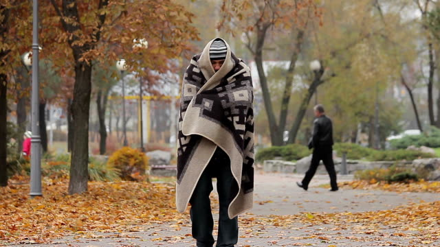 Helpless sick man feeling cold, wandering in city park covered with old blanket video