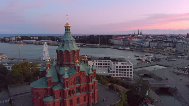 Helsinki Uspenski Cathedral Tours in Helsinki. The European Union. Sunset sky and clouds and Helsinki Uspenski Cathedral with colourful buildings. Helsinki, Finland. neoclassical architecture stock videos & royalty-free footage