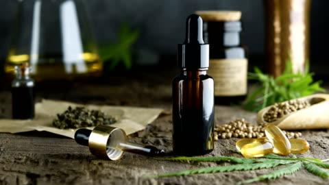 vidéos et rushes de huile essentielle de chanvre dans une petite bouteille en verre. récipient avec des feuilles de cannabis et des graines de cannabis sur le bois. - marchandise