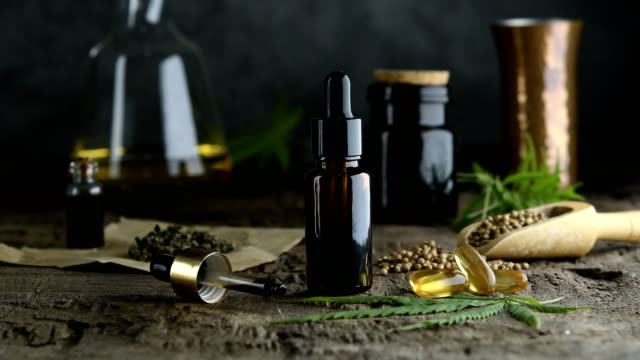 hemp essential oil in small glass bottle. container with cannabis leaves and cannabis seeds on wooden. hemp essential oil in small glass bottle. container with cannabis leaves and cannabis seeds on wooden. cannabidiol stock videos & royalty-free footage