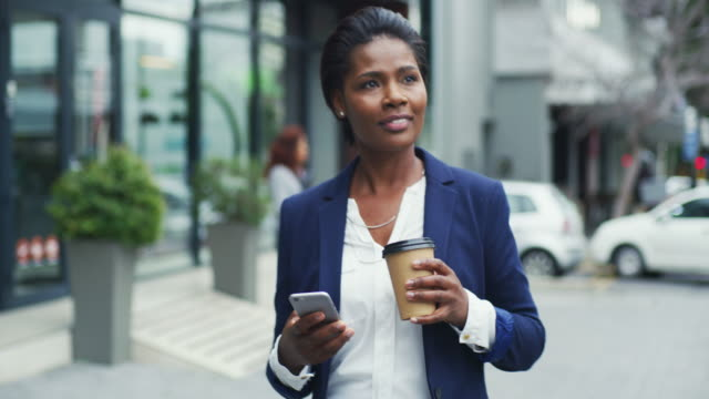 Her day seems to be on the right path Shot of a confident young businesswoman walking in the busy streets of the city to work while enjoying a cup of coffee outside during the day bolos stock videos & royalty-free footage