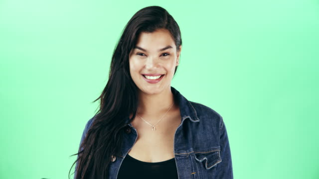 Her smile is something quite special 4k video footage of a confident young woman posing against a green studio background background color stock videos & royalty-free footage
