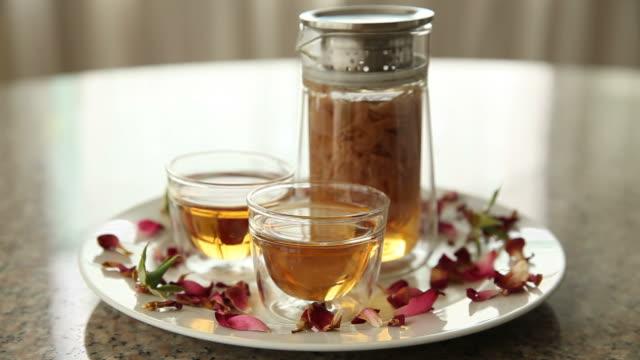 ört varmt te från rosa rosenblommor i en glaskopp med rosenblad, i naturligt ljus - tefat bildbanksvideor och videomaterial från bakom kulisserna