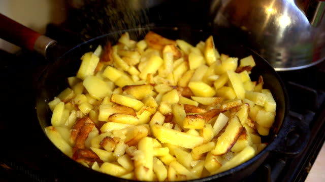 Herbs sprinkled potatoes, which is cooked in a cast iron pan on a gas stove video