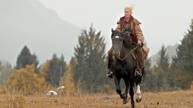 SLO MO DS Herdswoman monté sur un cheval au galop - Vidéo