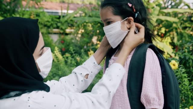 vidéos et rushes de ici, mettez votre masque avant d'aller à l'école, il vous protégera contre le virus. - enfant masque