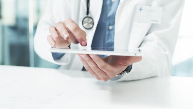 Here's how he keeps track of his patients' files 4k video footage of an unrecognizable male doctor using a digital tablet while sitting in his office general practitioner stock videos & royalty-free footage