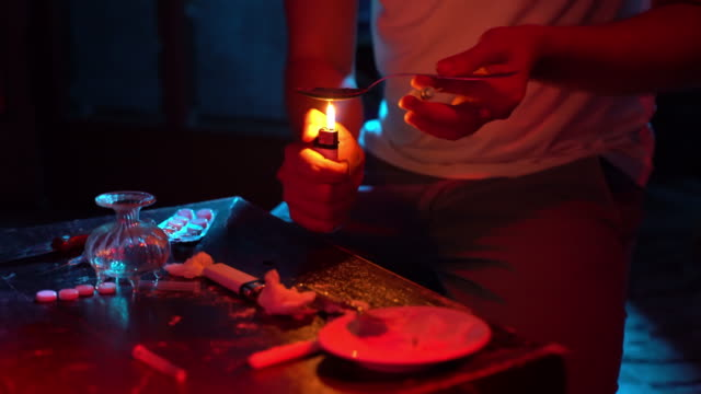 Heroin in powder and preparation process. Competent drug dealer cooking heroin, cocaine. Boiling narcotic on spoon in drug laboratory. Packaged doses and narcotic substance. Forbidden dangerous business. Drug abuse and criminal market concept