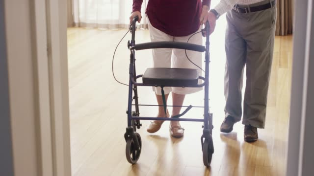 He's as helpful as ever 4k video footage of a senior man helping his wife with her walker through their retirement home orthopedic equipment stock videos & royalty-free footage
