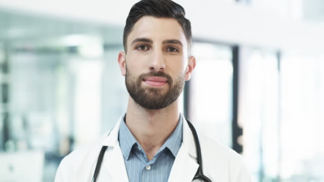 He's serious about his profession 4k video footage of a handsome young male doctor looking serious while standing in a hospital general practitioner stock videos & royalty-free footage