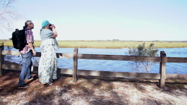 A heterosexual couple, man and woman, watching birds with a binocular in the Ochlockonee River State Park, North Florida. The man walking in to the scene when the woman already using binocular.