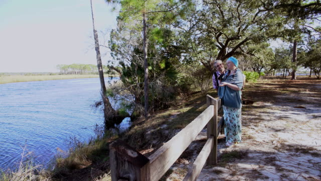 A heterosexual couple, man and woman, watching birds with a binocular in the Ochlockonee River State Park, North Florida.