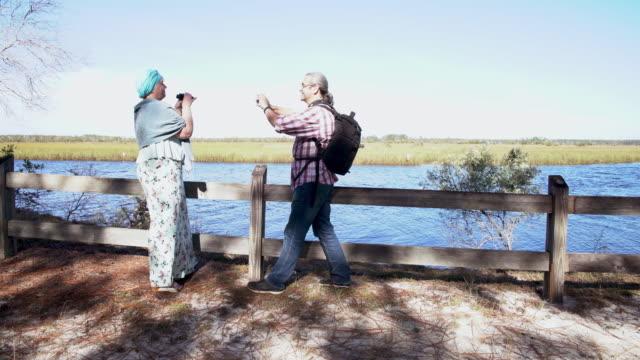 異性愛者のカップル、男女、オークロックネ川州立公園で双眼鏡で鳥を見て、ノースフロリダ。スマートフォンで女性の写真を撮っている男性。 - バードウォッチング点の映像素材/bロール