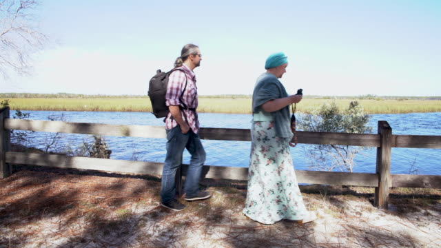 A heterosexual couple, man and woman, watching birds with a binocular, then they walking out. Ochlockonee River State Park, North Florida.
