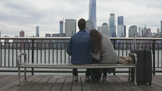 heterosexual couple travelers sitting on bench and waiting in new york city - bench stock videos & royalty-free footage