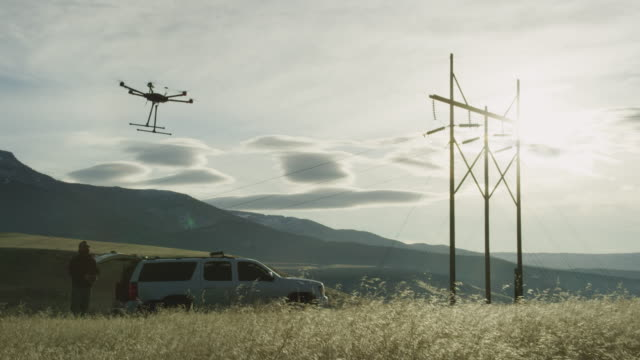 A Hexacopter Drone Lifts up into the Air in a Grassy Field while a Pilot/Operator Watches Next to an SUV and Some Power Lines on a Partly Cloudy Day Outdoors A Hexacopter Drone Lifts up into the Air in a Grassy Field while a Pilot/Operator Watches Next to an SUV and Some Power Lines on a Partly Cloudy Day Outdoors propeller stock videos & royalty-free footage