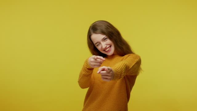 Hey you! Glad happy girl with brown hair in pullover smiling excitedly and pointing to camera