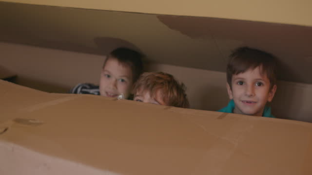Hiding in cardboard box, slow motion, handheld shot Three boys having fun hiding in cardboard box, slow motion, handheld shot elementary age stock videos & royalty-free footage