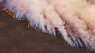 istock High aerial fly over view of a grass fire in the Okavango Delta, caused by drought and climate change, Botswana 1185163419