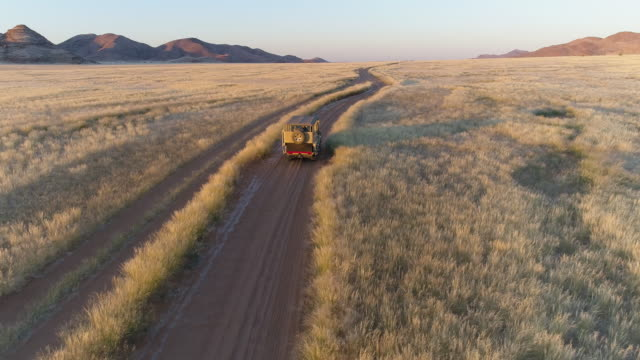 4K high aerial rear view of a 4x4 safari vehicle driving on a sand track through the African savannah grasslands with the famous fairy circles, Namibia 4K high aerial rear view of a 4x4 safari vehicle driving on a sand track through the African savannah grasslands with the famous fairy circles, Namibia country road stock videos & royalty-free footage