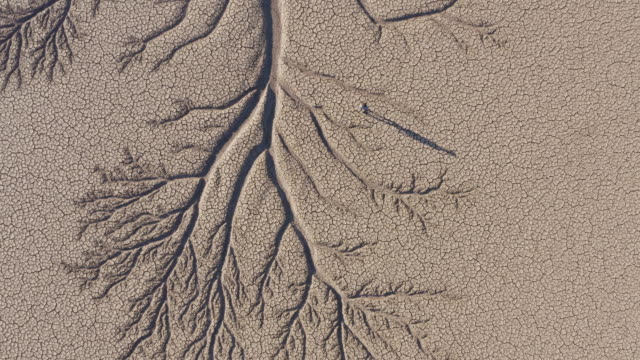 vídeos de stock e filmes b-roll de 4k high aerial zoom out view of a devastated farmer walking across the patterned cracked mud surface of a dry dam due to drought from climate change and global warming - paisagem árida