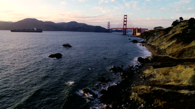 high angle above bakers beach in san francisco with golden gate bridge and cargo ship leaving bay area - ponte sospeso video stock e b–roll