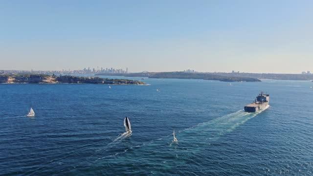 晴れた日にシドニー港に入るオーストラリア軍の大型揚陸艦の高角空中ドローン映像。左側のサウスヘッド半島、背景にシドニーcbdスカイライン。 - デイフェンス点の映像素材/bロール