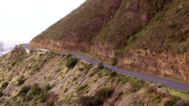 High angle drone shot of cyclist riding along mountain road video
