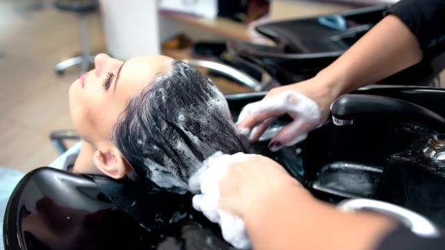 High angle female hands of professional hairdresser washing woman hair forming lathering High angle female hands of professional hairdresser washing woman hair forming lathering. Medium close-up young girl during shampooing head over sink at luxury modern beauty salon beauty salon stock videos & royalty-free footage