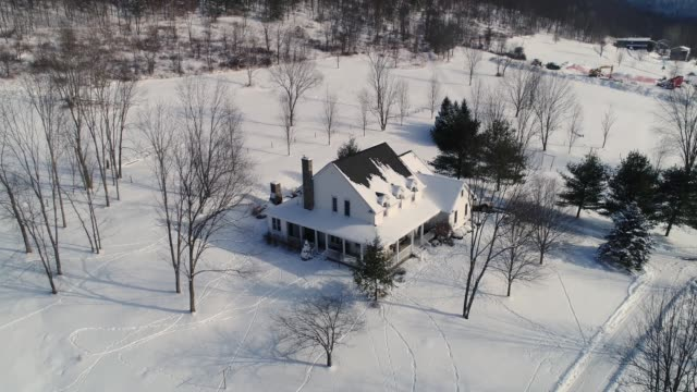 High Angle Forward Flyover Country House in Winter A high angle forward flyover of a typical snow-covered farmhouse in rural Pennsylvania in the winter. dormir stock videos & royalty-free footage