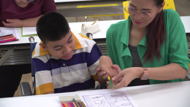 high angle front view: a teenage boy with a disability in wheelchair doing homework or assignment in the classroom with Asian beautiful teacher in school. The boy is sitting at a table, writing, drawing art in paper with color pencils with assistance.