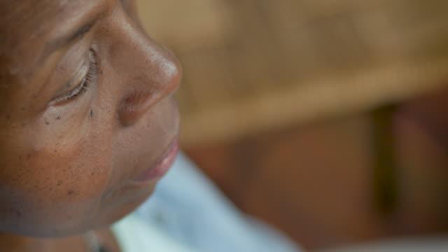 hochwinkelprofilansicht einer älteren schwarzen seniorin, die ruhig sitzt - geduld stock-videos und b-roll-filmmaterial